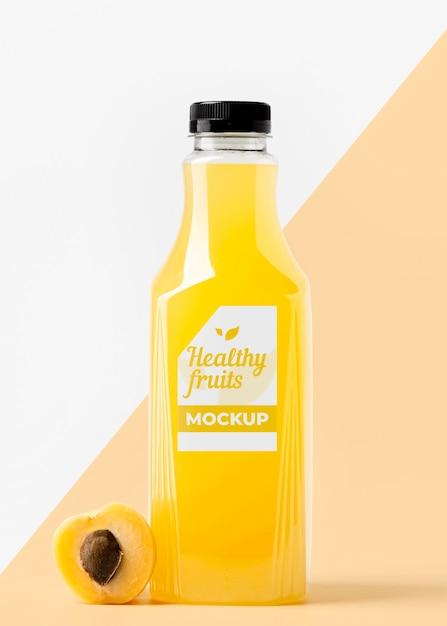 Vista frontal da garrafa de suco de pêssego com tampa Psd grátis