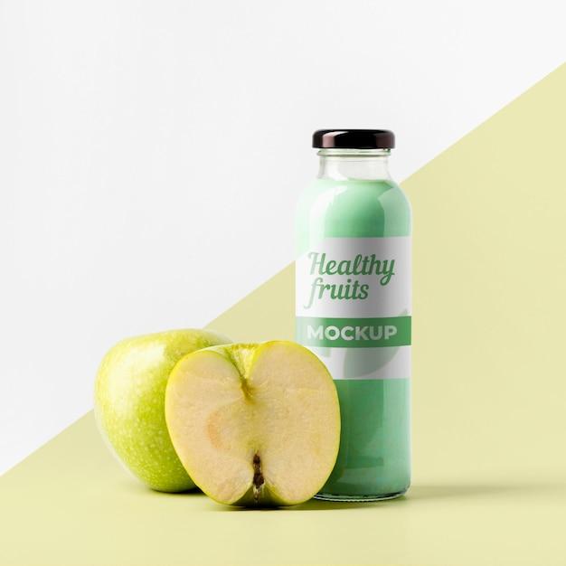 Vista frontal da garrafa de suco transparente com maçãs Psd grátis