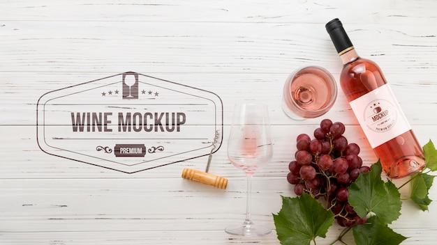 Vista frontal da garrafa de vinho rosa e uvas Psd grátis
