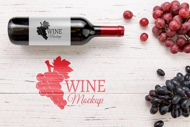 Vista frontal da garrafa de vinho tinto e uvas Psd grátis