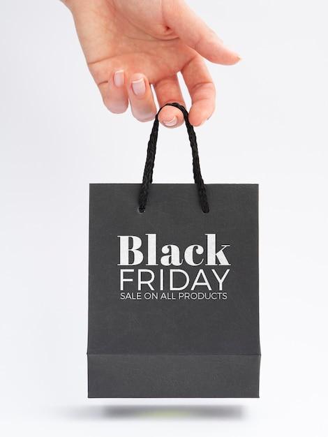 Vista frontal da mão segurando o conceito de saco preto sexta-feira Psd grátis