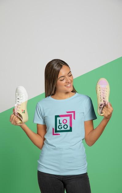 Vista frontal da mulher de camiseta segurando tênis Psd grátis