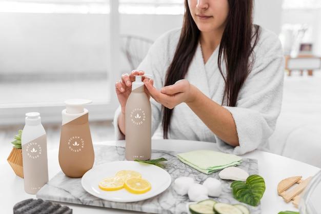 Vista frontal da mulher em casa usando hidratante Psd grátis