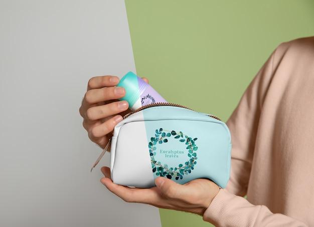 Vista frontal da mulher segurando a bolsa de maquiagem Psd grátis