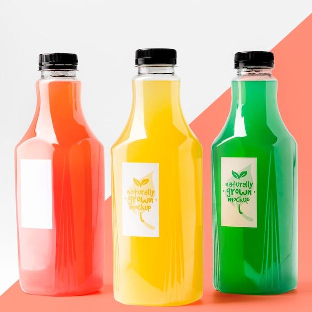 Vista frontal da seleção de garrafas de suco com tampas Psd grátis