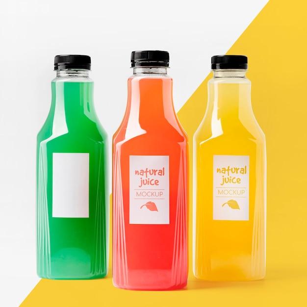 Vista frontal da seleção de garrafas de suco transparente Psd grátis