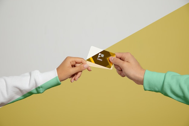 Vista frontal das mãos segurando cartões de visita Psd grátis