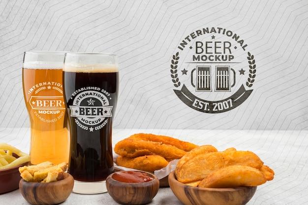 Vista frontal de copos de cerveja com variedade de lanches Psd Premium