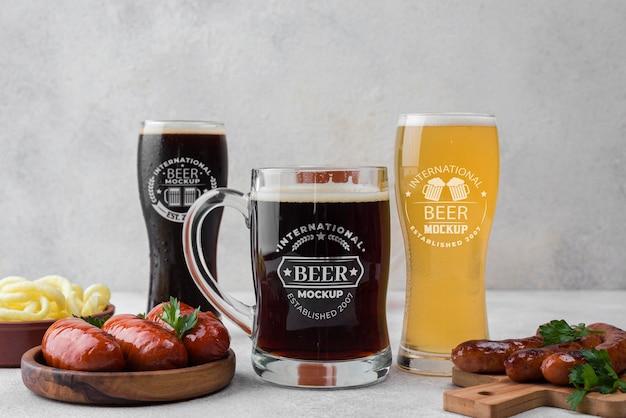 Vista frontal de copos de cerveja e canecas com lanche Psd grátis