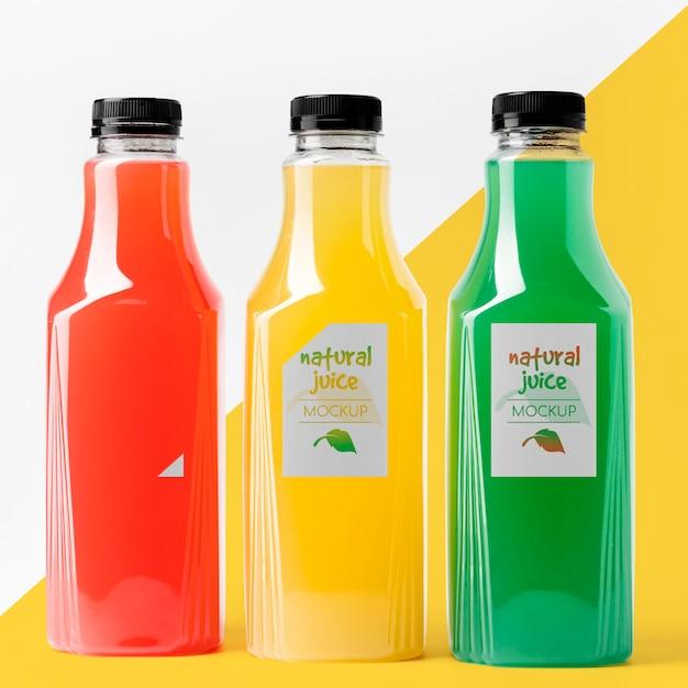 Vista frontal de diferentes garrafas de suco de vidro Psd grátis