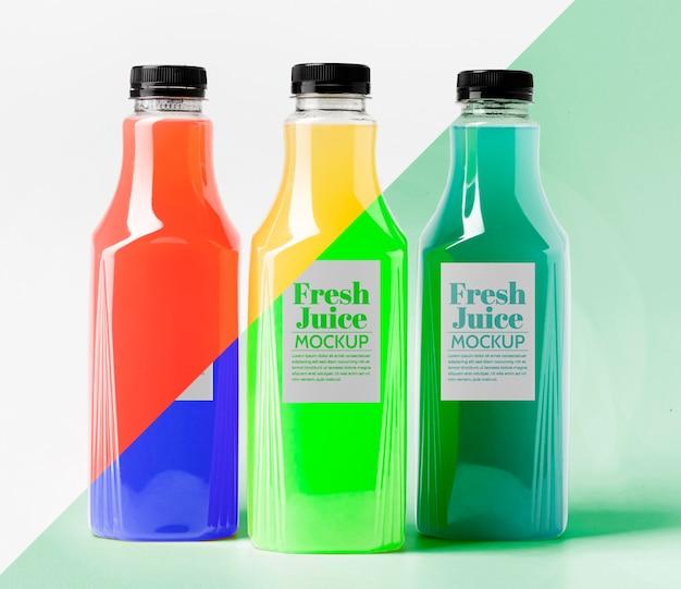 Vista frontal de diferentes garrafas de suco transparentes com tampas Psd grátis