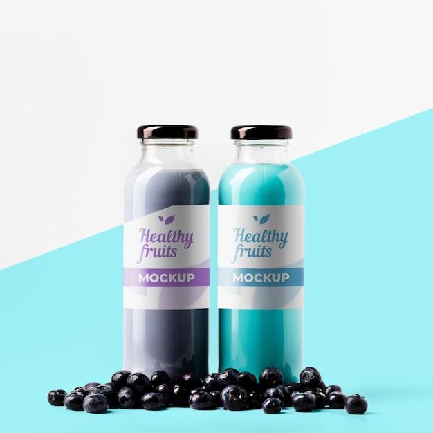 Vista frontal de garrafas de suco transparentes com mirtilos Psd Premium