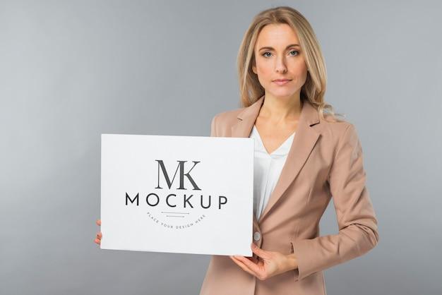 Vista frontal de uma mulher elegante segurando um cartaz em branco Psd Premium