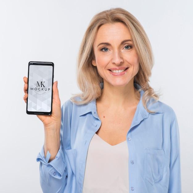 Vista frontal de uma mulher loira sorridente segurando um smartphone Psd grátis