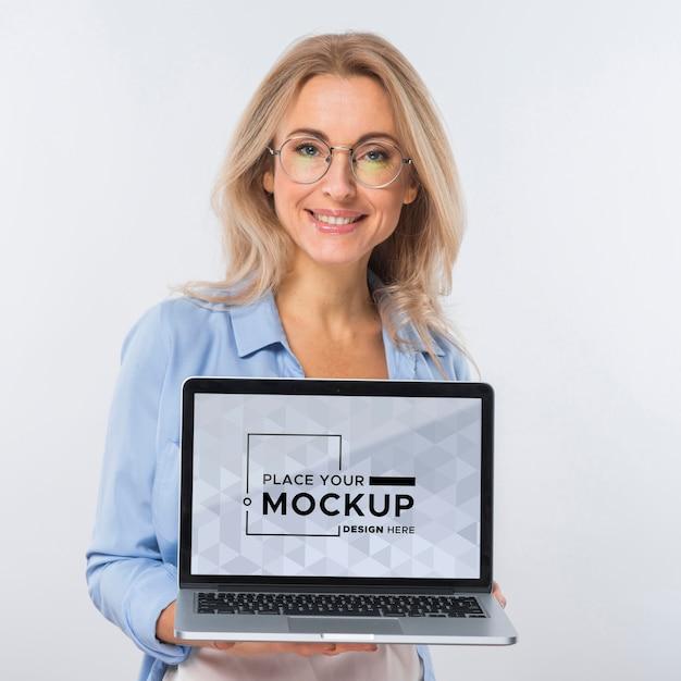 Vista frontal de uma mulher sorridente com óculos segurando um laptop Psd grátis