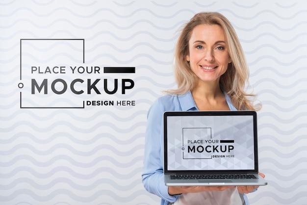 Vista frontal de uma mulher sorridente segurando um laptop Psd grátis