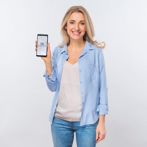 Vista frontal de uma mulher sorridente segurando um smartphone Psd grátis