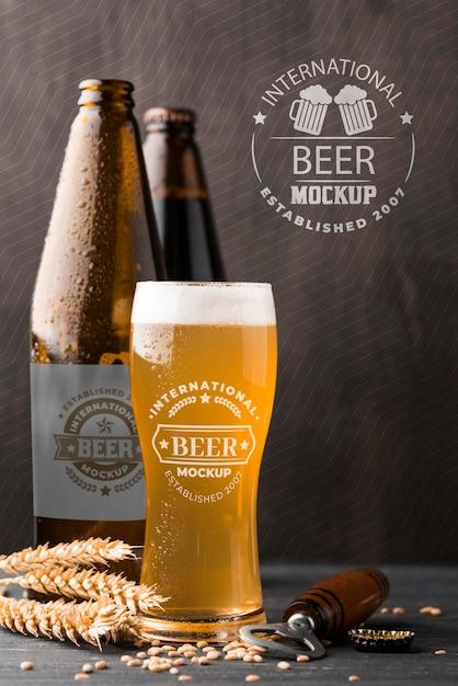 Vista frontal do copo de cerveja e garrafas com cevada Psd Premium
