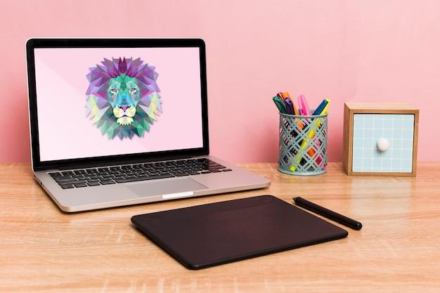 Vista frontal do laptop e bloco de desenho na mesa Psd grátis