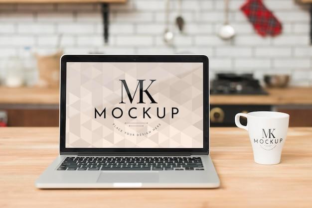 Vista frontal do laptop na cozinha com uma caneca de café Psd grátis