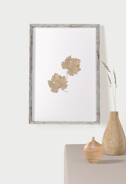 Vista frontal do quadro com folhas na parede e vasos Psd grátis