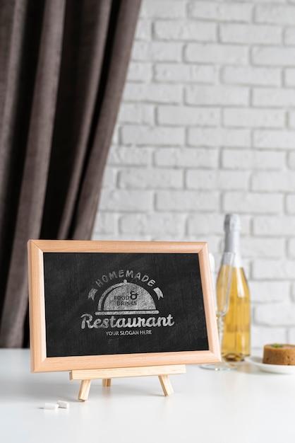 Vista frontal do quadro-negro com garrafa de vinho Psd grátis