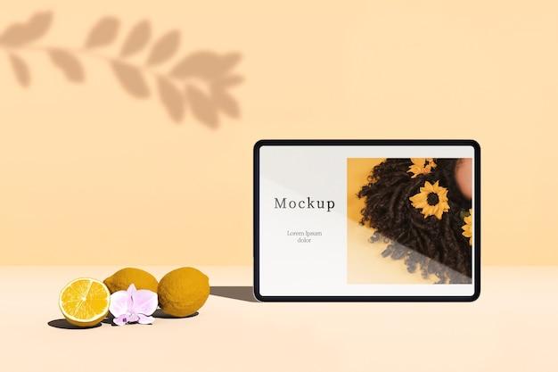Vista frontal do tablet com frutas cítricas e sombra Psd grátis