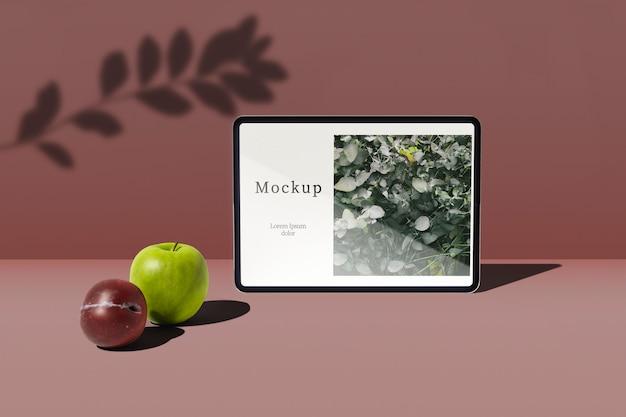 Vista frontal do tablet com maçã e ameixa Psd grátis