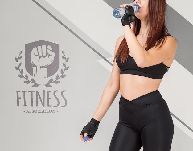 Vista lateral da aptidão mulher bebendo água para garrafa Psd grátis