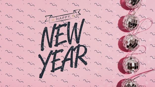 Vista superior ano novo letras com pequenos enfeites de bolas de discoteca Psd grátis