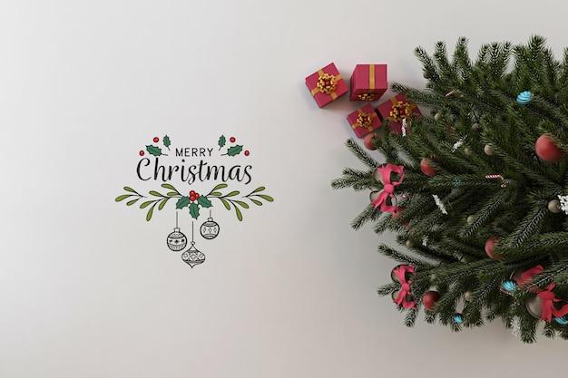 Vista superior da maquete de banner de feliz natal com árvore de natal e presentes Psd Premium