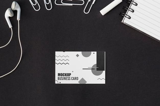 Vista superior da maquete do cartão de visita com fones de ouvido e clipes de papel Psd Premium