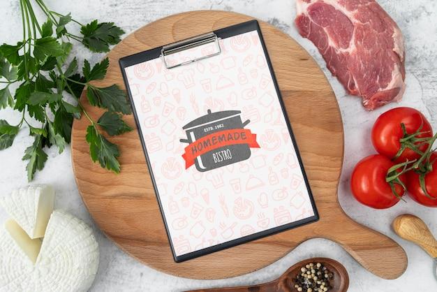 Vista superior de carne com menu e tomate Psd grátis