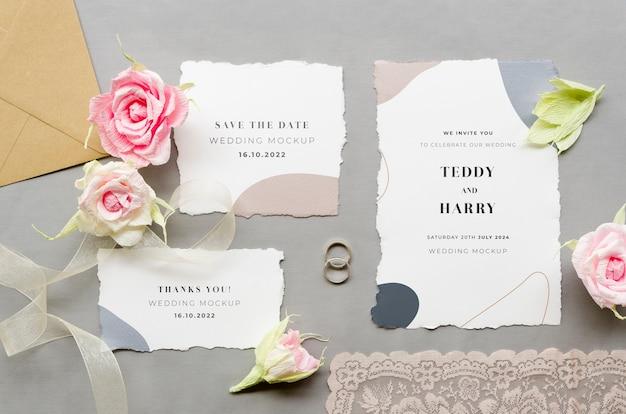 Vista superior de cartões de casamento com rosas e anéis Psd grátis