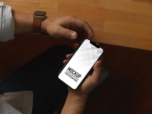 Vista superior de mãos masculinas usando smartphone enquanto está sentado na sala do escritório Psd Premium