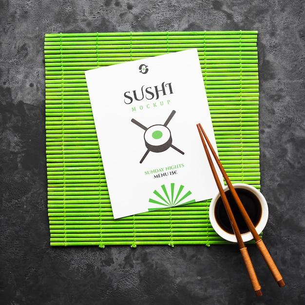 Vista superior de pauzinhos com molho de soja no rolo de bambu para sushi Psd grátis