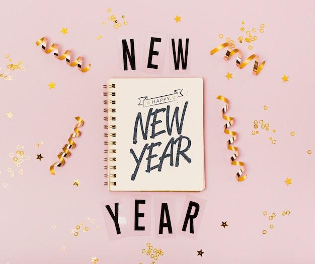 Vista superior do ano novo letras minimalistas no bloco de notas Psd grátis