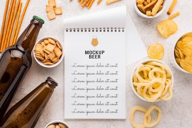 Vista superior do caderno com garrafas de cerveja e uma variedade de lanches Psd grátis