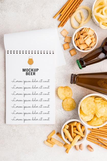 Vista superior do caderno com seleção de lanches e garrafas de cerveja Psd grátis