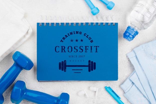 Vista superior do caderno de fitness com pular corda e pesos Psd grátis