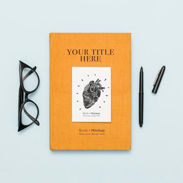 Vista superior do livro com caneta e óculos Psd grátis