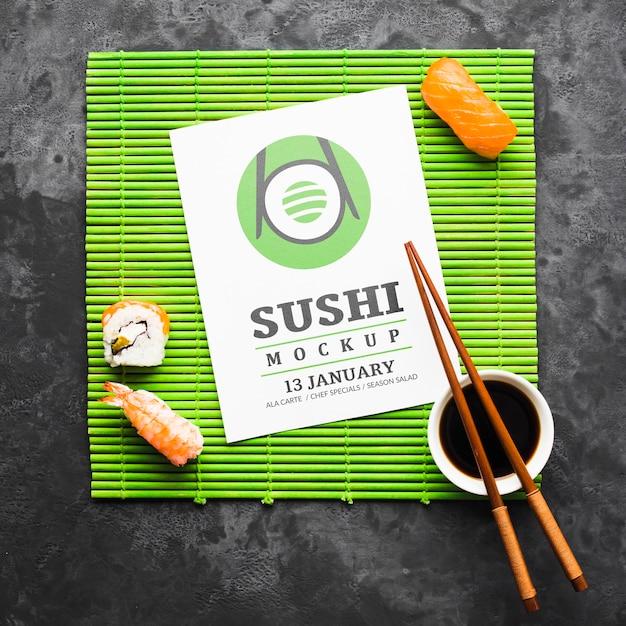 Vista superior do sushi com pauzinhos e molho de soja no rolo de bambu Psd grátis