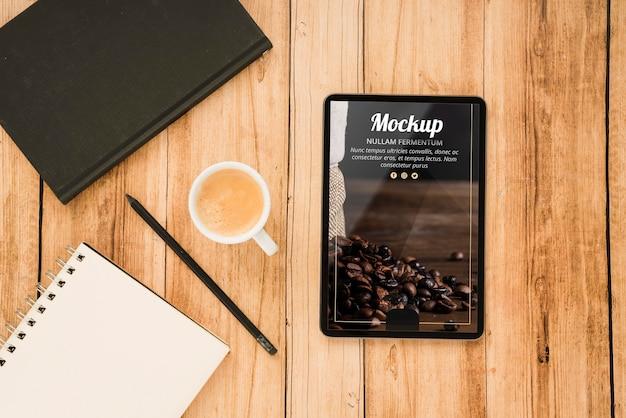 Vista superior do tablet com xícara de café e caderno Psd grátis