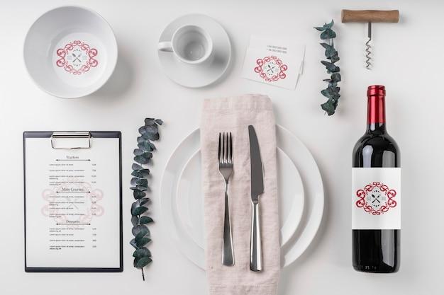 Vista superior garrafa de vinho com pratos e talheres Psd grátis