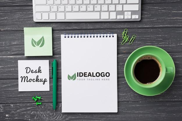 Vista superior mock-up notebook e artigos de papelaria perto de café e teclado Psd grátis