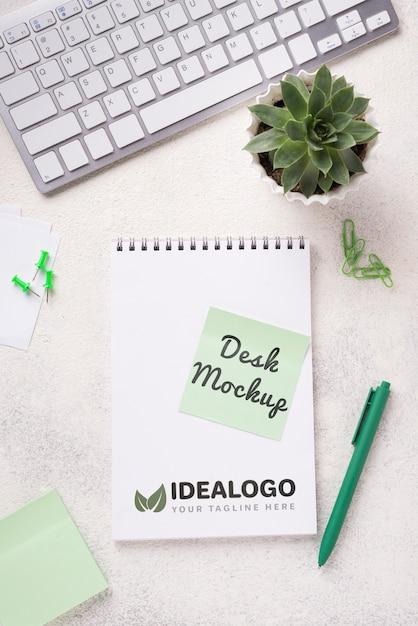 Vista superior mock-up notebook e artigos de papelaria perto de planta suculenta e teclado Psd grátis