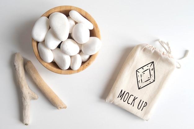 Zombar de saco de algodão ou bolsa e tigela com seixo branco e palitos de madeira rústicos na mesa branca Psd Premium