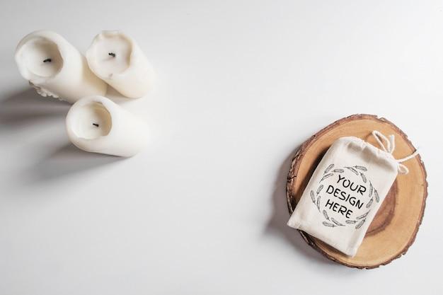 Zombar de saco de algodão ou bolsa na seção de árvore de corte de madeira e velas brancas na mesa branca Psd Premium