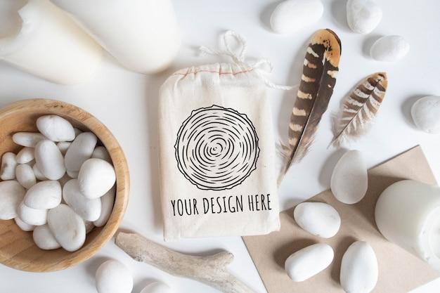 Zombe de saco de algodão ou bolsa e tigela com elementos de seixo e boho brancos na mesa branca. Psd Premium