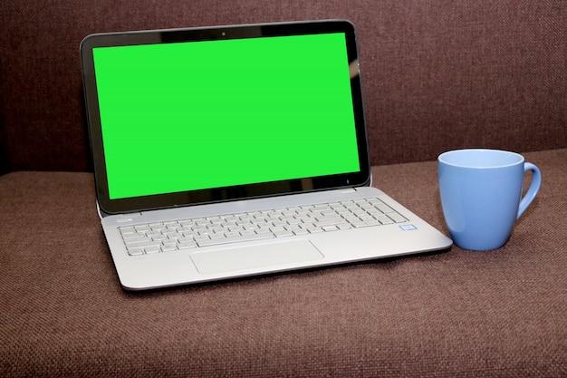 Blank Screen Laptop mit einem Teetasse auf einem braunen Hintergrund Kostenlose PSD